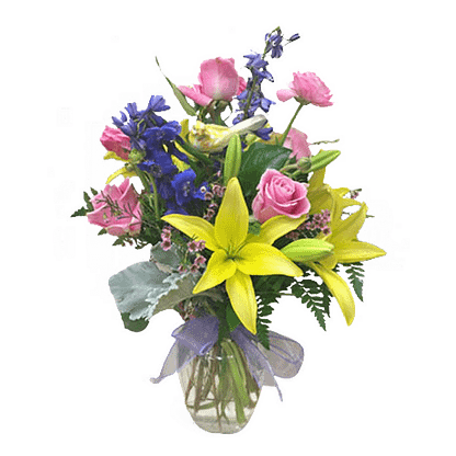 Flower arrangement for All Occasions with ranunculus, daylilies, roses and more arranged in a glass vase
