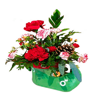 Christmas flower arrangement with carnations, mini carnations, pine cone, berries and greenery arranged in elf shoe