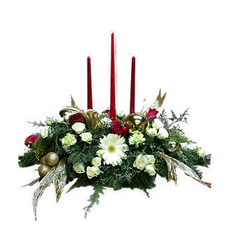 Christmas centerpiece with roses, gerberas, spray roses, carnations, evergreens, limonium, ornament balls, ribbon and candles