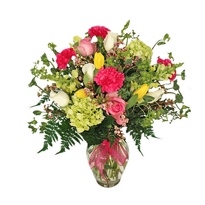 Flower arrangement for any occasion with roses, carnations, green hydrangea, and more arranged in a glass vase with pink ribbon