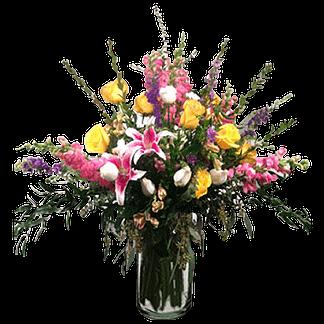 Flower arrangement with roses, stargazer lilies, snapdragons, larkspur, alstroemeria, and foliage arranged in a glass vase