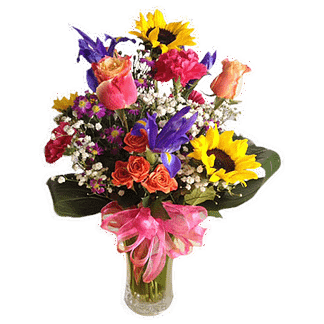 Flower arrangement for any occasion with roses, sunflowers, iris, carnations, baby's breath, and foliage. Arranged in a glass vase with pink bow