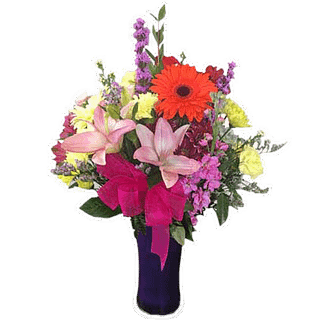 Flower arrangement for any occasion with lilies, stock, liatris, gerberas, limonium, pompons, alstroemeria and greenery, arranged in a blue vase with a pink bow.