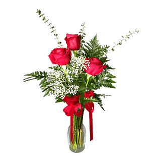 3 roses arranged in a bud vase decorated with a red bow